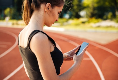 Side view of a beautiful woman resting after run and using smartphone on outdoor stadium Stock Photo