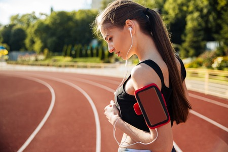 Side view of a female runner listening to music with mobile phone at the stadium