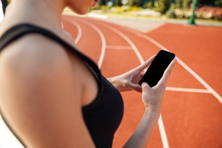 racetrack: Cropped image of a beautiful woman resting after run and using smartphone on outdoor stadium Stock Photo