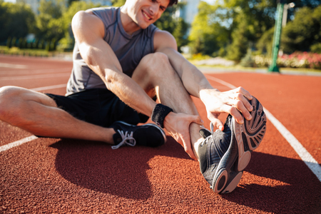 Cropped image of a runner suffering from leg cramp at the stadium