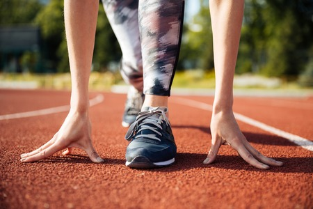Cropped image of a female sprinter getting ready to start running at the stadium Stock Photo