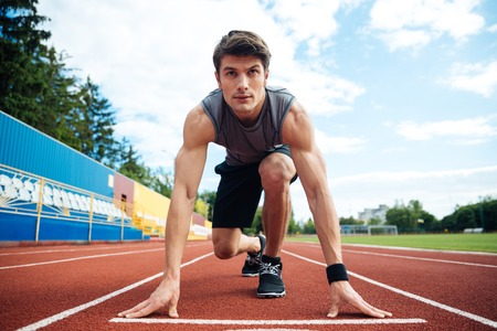 Young handsome man in starting position for running on sports track Stock Photo