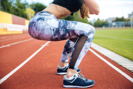 squats: Closeup of slim woman athlete exercising and doing squats on stadium Stock Photo