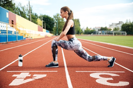 Pretty young woman athlete working out on stadium Stock Photo