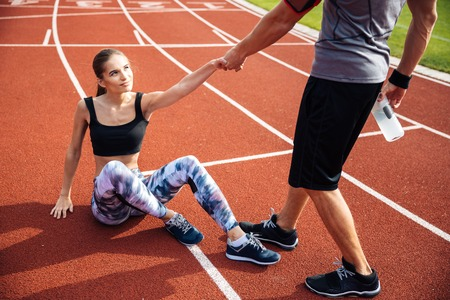 Cropped image of a fitness man with water bottle helping young girl to get up at the stadium Фото со стока