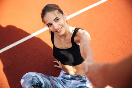 levantandose: Smiling attractive young woman athlete getting up and taking somebody hand on stadium