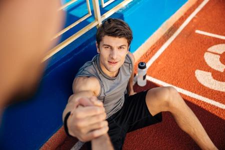 Uomo di forma fisica con la bottiglia di acqua ha bisogno di aiuto per arrivare fino allo stadio
