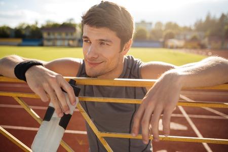 Deportista joven con una botella de agua en reposo en la barandilla en el estadio
