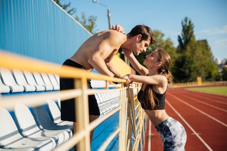 participant: Young beautiful sports couple in love hugging on athletics track field at the stadium
