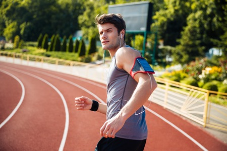 sport fitness: Male runner listening to music with mobile phone at the stadium and looking at camera