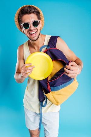 배낭에서 프리즈 비 디스크를 복용하는 모자와 선글라스에 쾌활 한 젊은 남자