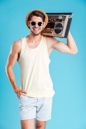 grabadora: joven atractiva alegre en el sombrero y gafas de sol de pie y sosteniendo estéreo portátil sobre fondo azul
