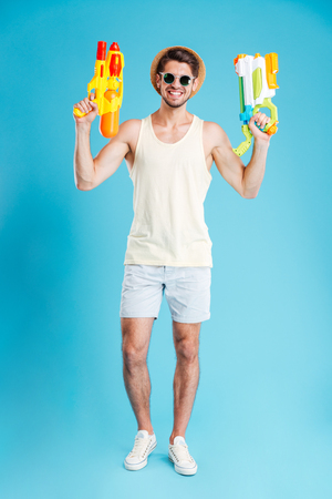 Full length of cheerful young man holding two water guns Stock Photo