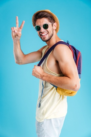 Smiling young man in hat and sunglasses with backpack showing peace sign