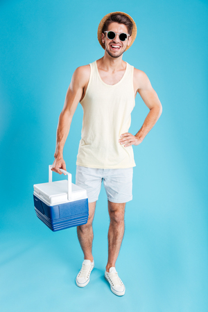 frig: Cheerful young man in hat and sunglasses standing and holding cooler bag