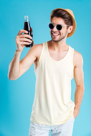 Smiling young man in hat and sunglasses standing and holding bottle of soda