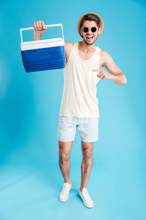Happy young man in hat and sunglasses holding and pointing on cooler bag
