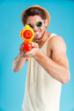 Sonriente joven en el sombrero y gafas de sol jugando con pistola de agua sobre fondo azul