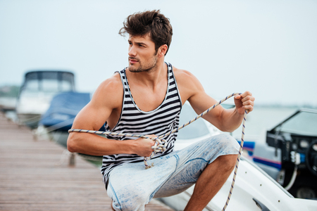 Young handsome man preparing boat to start a journe at the pier Stock Photo