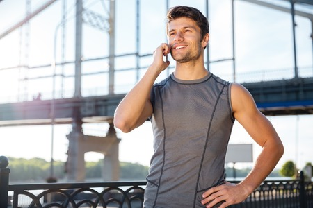 sports uniform: Handsome young man in sports uniform is talking on the mobile phone while standing at the bridge