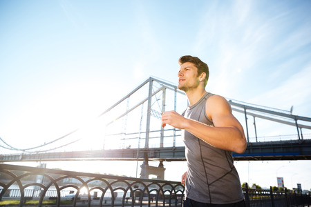 Handsome sports man running along big modern bridge at sunset light