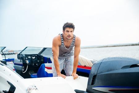 彼のモーター ボートで若い船乗りの男