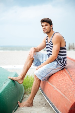 upturned: Handsome young man sitting on a fishing boat and looking away by the sea Stock Photo