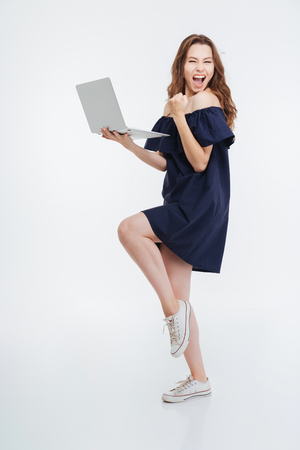 hurray: Full length of cheerful excited young woman holding laptop and celebrating success over white background