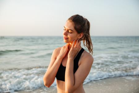 Portret van een mooie jonge meisjeszitting in openlucht bij het strand Stockfoto