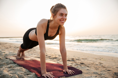 beach mat: Portrait of a young woman stretching on yoga mat outdoors at the beach