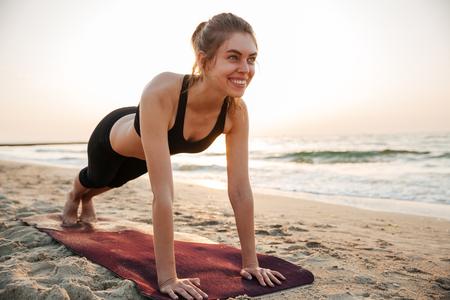 Portrait d'une jeune femme d'étirement sur un tapis de yoga en plein air à la plage