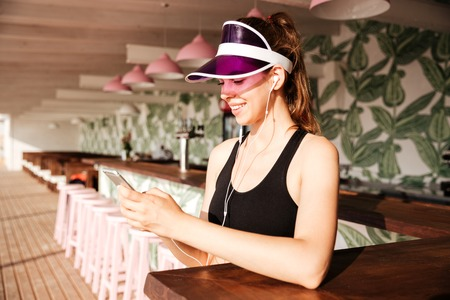 sportwoman: Young attractive sports woman listens music with earphones and smartphone in her hands in cafe Stock Photo