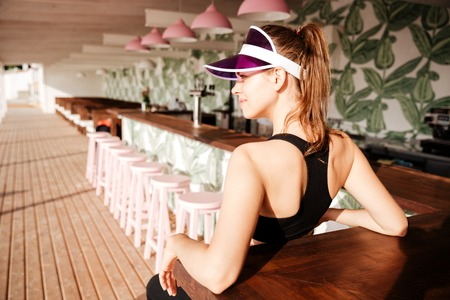 sportwoman: Young beautiful sports woman resting after workout in a beach cafe on palm leaves pattern background Stock Photo