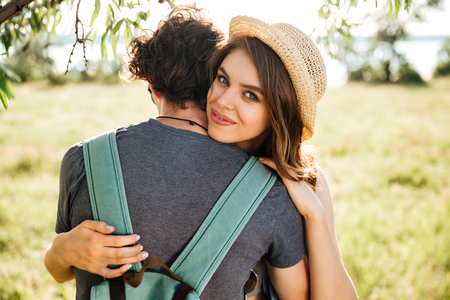 Two young hipster lovers hugging in the forest Stock Photo