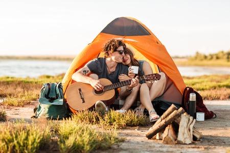 彼のガール フレンドは、ビーチでのキャンプのギターを弾く男の肖像