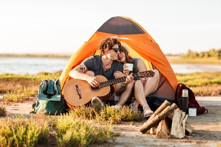 Portrait of a man playing guitar for his girlfriend camping at the beach 版權商用圖片
