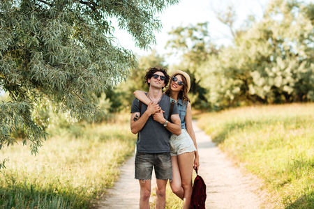 Young attractive hipster couple standing against trees on the background and hugging