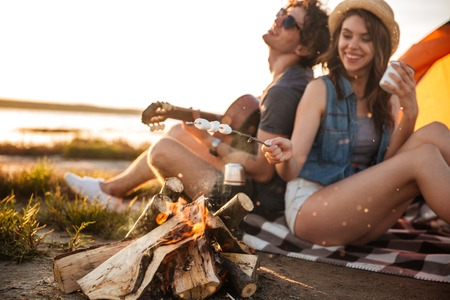 Cheerful beautiful young couple playing guitar and frying marshmallows on bonfire Banco de Imagens