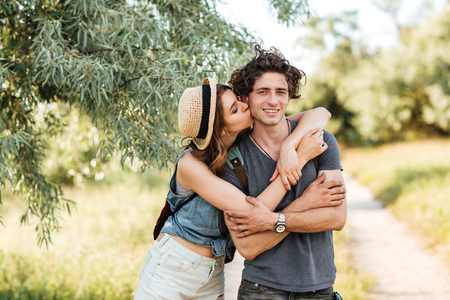 hogging: Young attractive hipster couple standing against trees on the background kissing and hugging Stock Photo