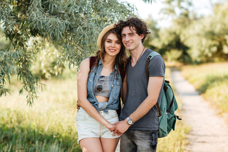 hogging: Young attractive hipster couple standing against trees on the background and holding hands