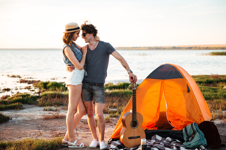 Portrait of happy young attractive couple embracing in front of camping tent Stock Photo