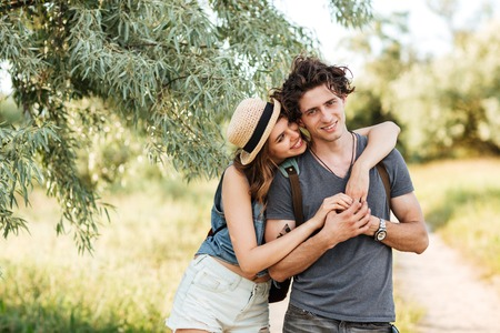 hogging: Young attractive hipster couple standing against trees on the background and hugging