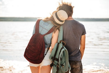 Young couple in love standing backwards hugging and looking at the seaside Stock Photo