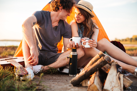 Cropped image of a young couple drinking tea at the bonfire while camping Stock Photo