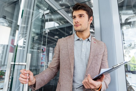 the entering: Attractive young businessman holding clipboard and entering the door in office Stock Photo