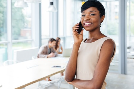 Happy african american young businesswoman standing in office and talking on cell phone Stock Photo