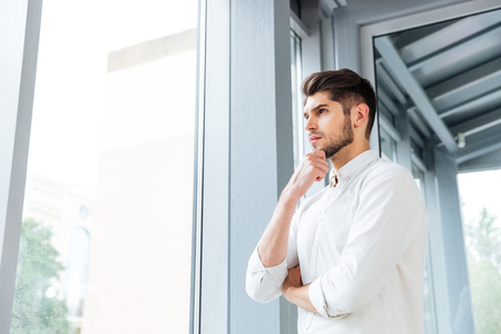 stubbly: Thoughtful young man standing near the window and thinking