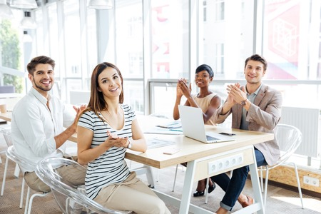 Multiethnic group of happy young business people applauding at meeting in office Stock Photo