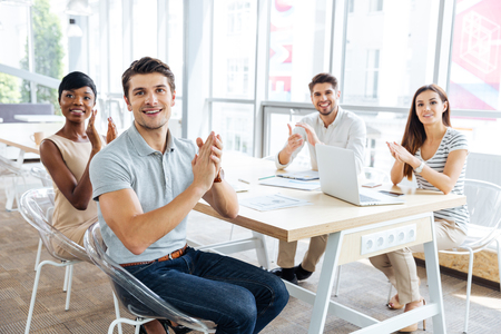 Group of cheerful young business people sitting on presentation in office and clapping