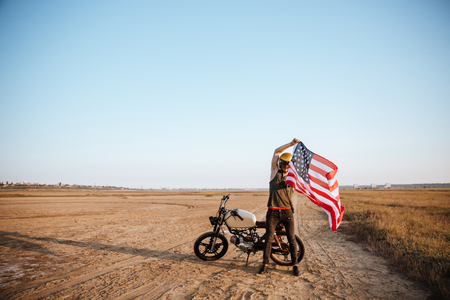 racer flag: Man in golden helmet holding american flag at the desert with motorcycle on the background